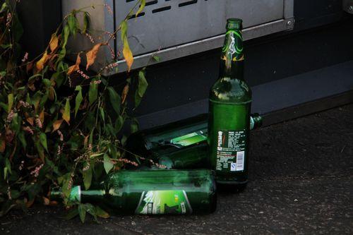 休闲公园变为饮酒场所.桥边小园桌旁的垃圾边,堆放着几个啤酒瓶.图片