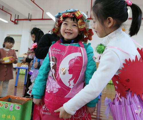 幼儿园的小朋友们穿着自制的环保服装展示自己动手